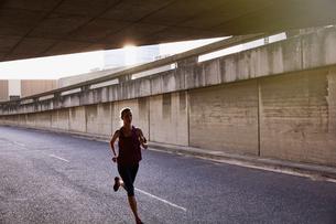 Female runner running into urban tunnelの写真素材 [FYI02178286]