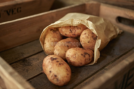Still life close up rustic fresh, organic, healthy dirty potatoes in bag in wooden crateの写真素材 [FYI02178292]