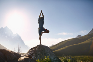 Young man balancing in tree pose on rock in sunny, remote valleyの写真素材 [FYI02178298]