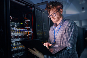 Focused male IT technician working at laptop in dark server roomの写真素材 [FYI02178339]