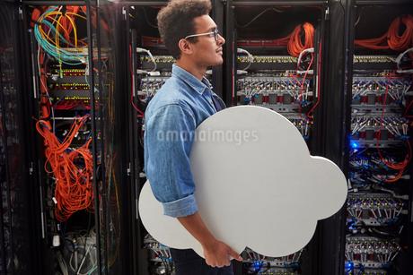 Male IT technician carrying cloud in server room, cloud computingの写真素材 [FYI02178341]