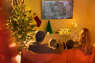Family watching TV in Christmas living roomの写真素材 [FYI02178376]