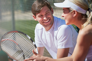 Smiling male and female tennis players resting and talking with tennis rackets in sunny outdoorsの写真素材 [FYI02178382]
