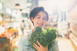 Portrait smiling young woman holding fresh kale in grocery store marketの写真素材 [FYI02178415]