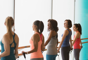 Smiling women exercising with resistance bands in gym studioの写真素材 [FYI02178416]