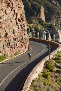 Male triathlete cyclist cycling uphill along sunny cliffsの写真素材 [FYI02178421]