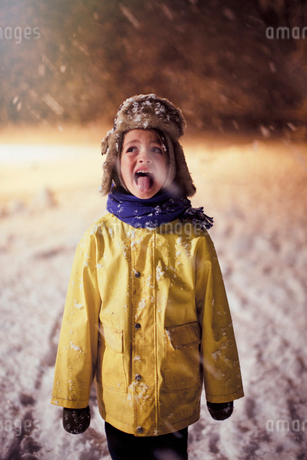 Boy in warm clothing sticking tongue out, tasting snowの写真素材 [FYI02178440]