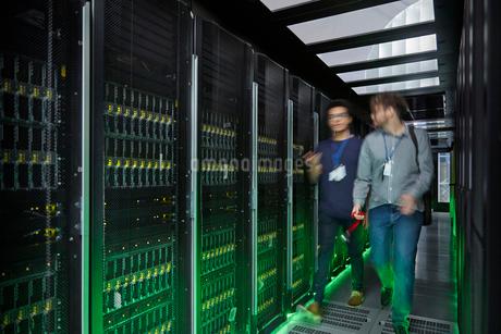 IT technicians walking and talking in dark server roomの写真素材 [FYI02178457]