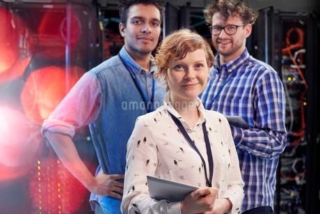Portrait confident IT technicians with digital tablet in server roomの写真素材 [FYI02178502]
