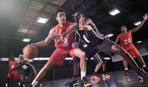 Young male basketball players playing on court in gymnasiumの写真素材 [FYI02178518]