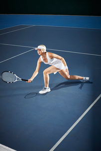 Young female tennis player playing tennis, reaching with tennis racket on blue tennis courtの写真素材 [FYI02178553]