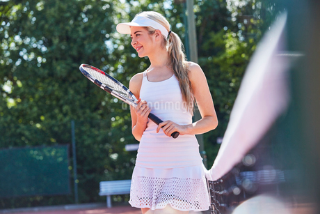 Smiling young female tennis player holding tennis racket along sunny netの写真素材 [FYI02178560]