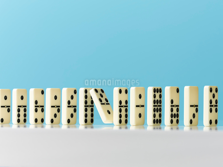 Falling in domino in a row on blue backgroundの写真素材 [FYI02178573]
