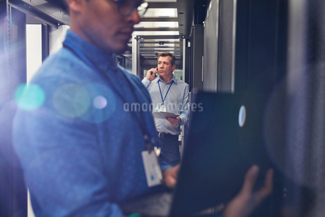 Male IT technicians using laptop and talking on cell phone in server roomの写真素材 [FYI02178614]