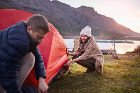 Young couple pitching tent at lakeside campsiteの写真素材 [FYI02178627]