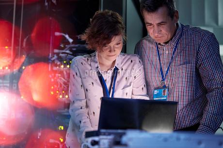 IT technicians working at laptop in dark server roomの写真素材 [FYI02178631]