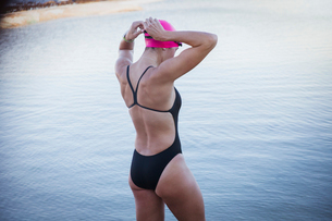 Female open water swimmer adjusting swimming goggles at oceanの写真素材 [FYI02178636]
