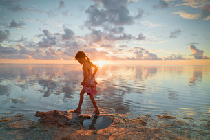 Girl wading in ocean surf on tranquil sunset beachの写真素材 [FYI02178645]