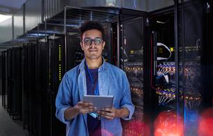 Portrait confident male IT technician with digital tablet in server roomの写真素材 [FYI02178649]