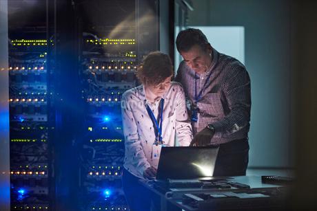 IT technicians working at laptop in dark server roomの写真素材 [FYI02178668]