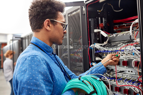 Male IT technician plugging cable into panel in server roomの写真素材 [FYI02178676]