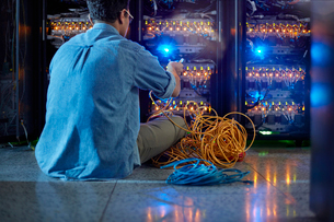 Male IT technician with cables at panel in dark server roomの写真素材 [FYI02178713]