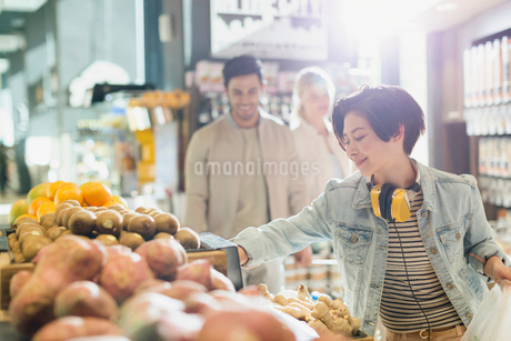 Young woman with headphones grocery shopping, browsing produce in marketの写真素材 [FYI02178721]