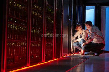 IT technicians talking at glowing panel in dark server roomの写真素材 [FYI02178731]