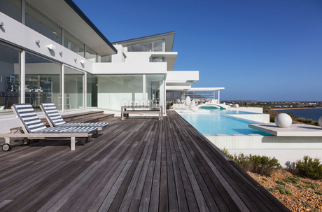 Sunny modern luxury home showcase exterior patio with infinity poolの写真素材 [FYI02178732]