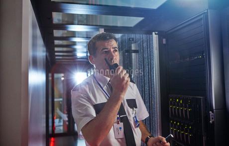 Male security guard using walkie-talkie in dark server roomの写真素材 [FYI02178749]