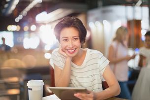 Portrait smiling young woman using digital tablet and drinking coffee in cafeの写真素材 [FYI02178771]