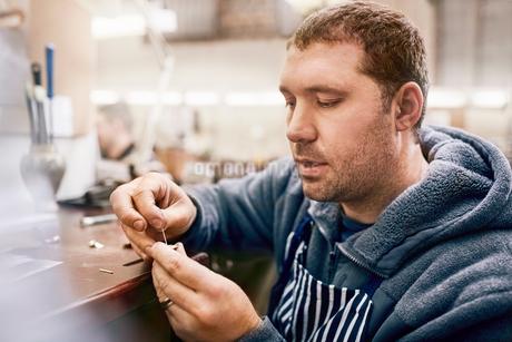 Focused male jeweler making jewelry in workshopの写真素材 [FYI02178786]
