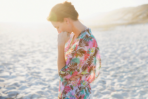 Serene brunette woman in swimsuit coverup on sunny summer beachの写真素材 [FYI02178800]