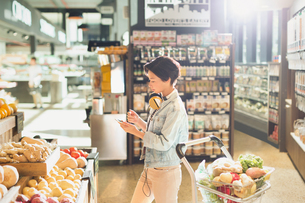 Young woman with headphones using cell phone, grocery shopping in marketの写真素材 [FYI02178823]
