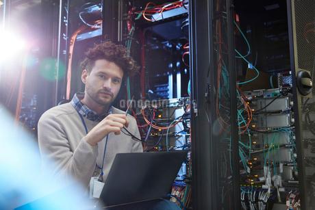 Portrait confident male IT technician working at laptop in server roomの写真素材 [FYI02178853]