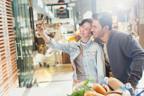 Young couple taking selfie grocery shopping in marketの写真素材 [FYI02178859]
