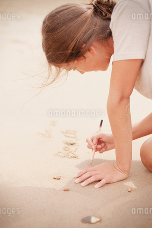 Teenage girl with stick writing in sand on summer beachの写真素材 [FYI02178878]