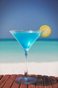 Blue cocktail with lemon slice in martini glass on sunny tropical beachの写真素材 [FYI02178893]