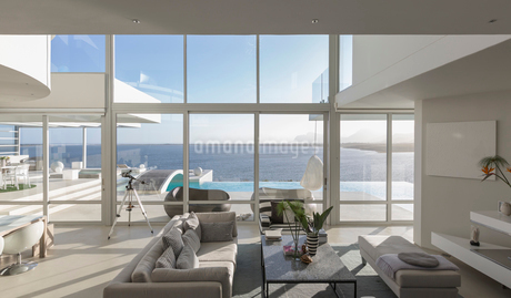 Sunny, tranquil modern luxury home showcase interior living room with patio and ocean viewの写真素材 [FYI02178898]
