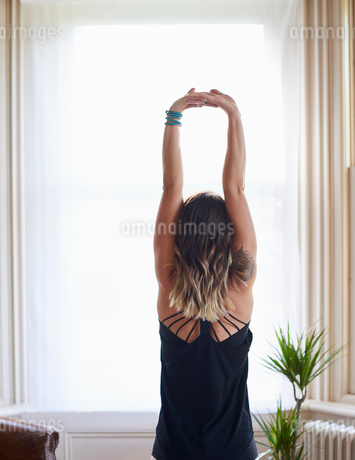 Woman practicing yoga, stretching arms overhead at windowの写真素材 [FYI02178914]