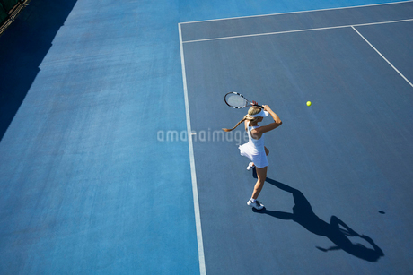 Overhead view young female tennis player playing tennis on sunny blue tennis courtの写真素材 [FYI02178938]