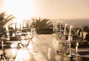 Glasses on sunny sunset patio tableの写真素材 [FYI02178944]