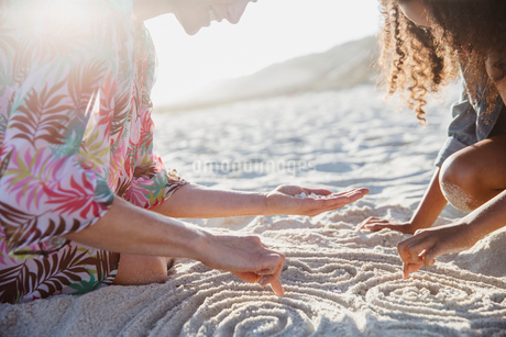 Mother and daughter drawing spirals in the sand on sunny summer beachの写真素材 [FYI02178956]