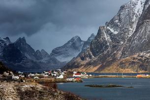 Fishing village at waterfront below snowy, rugged mountains, Reine, Lofoten, Norwayの写真素材 [FYI02178960]