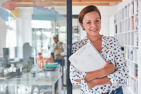 Portrait confident businesswoman with notebook in officeの写真素材 [FYI02178985]