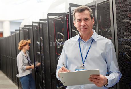 Portrait confident male IT technician with clipboard in server roomの写真素材 [FYI02178990]