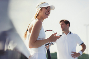 Laughing female tennis player holding cell phone and tennis racketの写真素材 [FYI02179000]