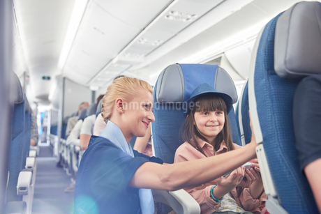 Flight attendant helping girl passenger on airplaneの写真素材 [FYI02179008]