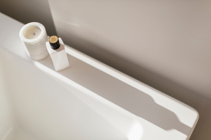 Candle and bottle casting shadow on ledge of white bathtubの写真素材 [FYI02179035]