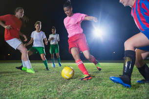 Young female soccer players playing soccer on field at nightの写真素材 [FYI02179084]